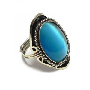 Handmade oval-shaped cat's eye glass bead cabochon on adjustable alpaca silver metal ring with rope edge border in turquoise blue color.