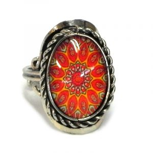 Handmade small oval-shaped acrylic New Age themed psychedelic floral mandala graphic design on alpaca silver metal ring with rope edge border in orange, red, and golden yellow color com