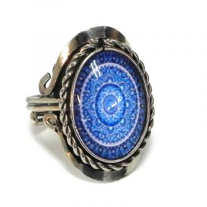 Handmade small oval-shaped acrylic New Age themed mandala graphic design on alpaca silver metal ring with rope edge border in blue, light blue, and white color combination.