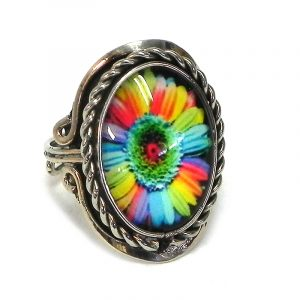 Handmade small oval-shaped acrylic New Age themed daisy flower graphic design on alpaca silver metal ring with rope edge border in rainbow color combination.