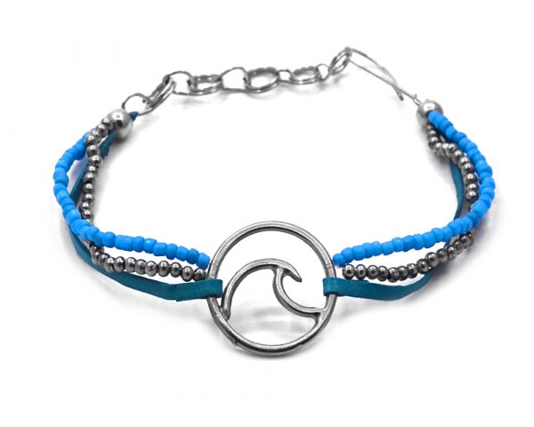 Suede vegan leather and seed bead multi strand bracelet with silver metal round wave charm centerpiece in turquoise blue and teal color combination.
