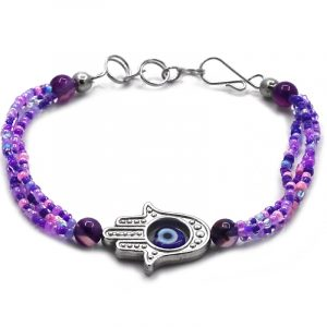 Seed bead multi strand bracelet with silver metal hamsa hand charm and blue evil eye bead centerpiece in purple, lavender, light pink, and indigo color combination.