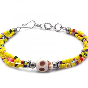 Seed bead multi strand bracelet with skull shaped magnesite gemstone centerpiece in yellow, white, beige, and multicolored color combination.