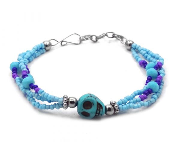 Seed bead and crystal bead multi strand bracelet with skull shaped tumbled magnesite gemstone centerpiece in light blue, turquoise, purple, and indigo color combination.