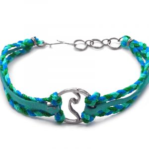 Suede vegan leather and braided macramé thread multi strand bracelet with silver metal round wave charm centerpiece in teal, turquoise blue, and green color combination.