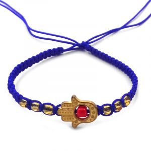 Handmade macramé braided string bracelet with gold-colored metal hamsa hand charm and seed bead centerpiece in blue and red color combination.