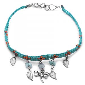 Handmade floral seed bead strap anklet with chip stones, silver metal dragonfly charm, and leaf charm dangles in turquoise mint, orange, and black color combination.