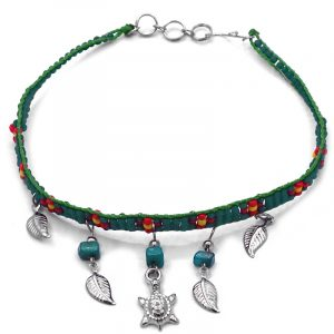 Handmade floral seed bead strap anklet with chip stones, silver metal sea turtle charm, and leaf charm dangles in green, dark teal, red, and yellow color combination.