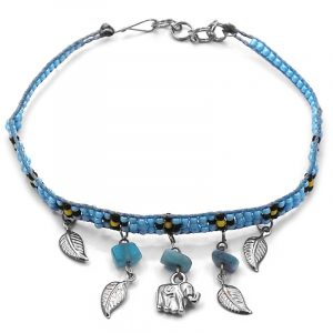 Handmade floral seed bead strap anklet with chip stones, silver metal elephant charm, and leaf charm dangles in light blue, black, and yellow color combination.