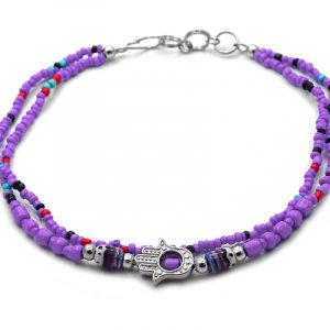 Handmade seed bead multi strand anklet with silver metal hamsa hand charm and tribal pattern bead centerpiece in purple, red, and mint turquoise color combination.