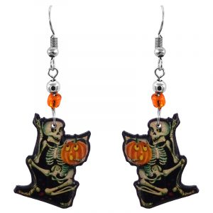 Handmade Halloween themed skeleton holding pumpkin graphic acrylic dangle earrings with beaded metal hooks in beige, black, orange, and yellow color combination.